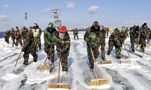 Sailors aboard the USS Ronald Reagan wash down the flight deck to remove potential radiation contamination while operating off the coast of Japan providing humanitarian assistance in support of Operation Tomodachi, March 22, 2011.