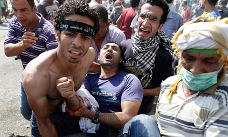 Supporters of Egypt's ousted president Mohamed Morsi carry a wounded man during clashes with security forces in Cairo. (Photograph: Hassan Ammar/AP)