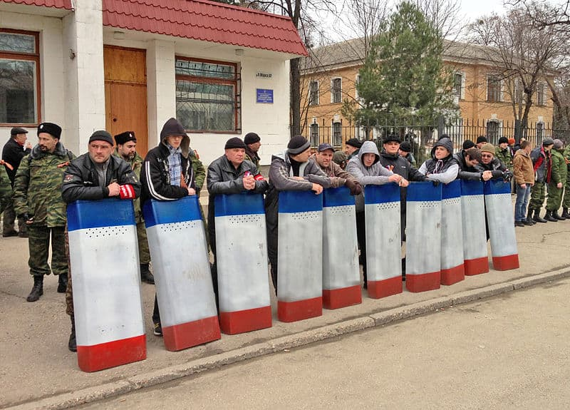 A Crimean self-defense militia stands guard with riot shields painted in the Crimean tricolor flag