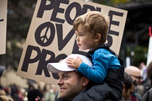 "A sign reads ""People Over Profits"" behind a child on a man's shoulders at a protest. Luciano Castillo (CC BY 2.0)"
