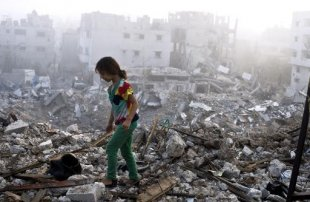 A Palestinian girl walks on the rubble strewn ceiling of her family's home after she and other members of her family returned on August 27, 2014 to Gaza City's Shejaiya neighbourhood