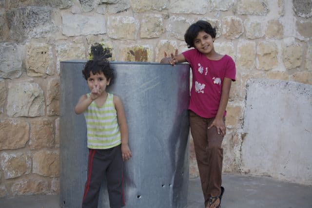 Girls show their water tank, which has bullet holes from Israeli settlers, so the family can't use it. (Photo: Sara Apps @ flickr.cc)