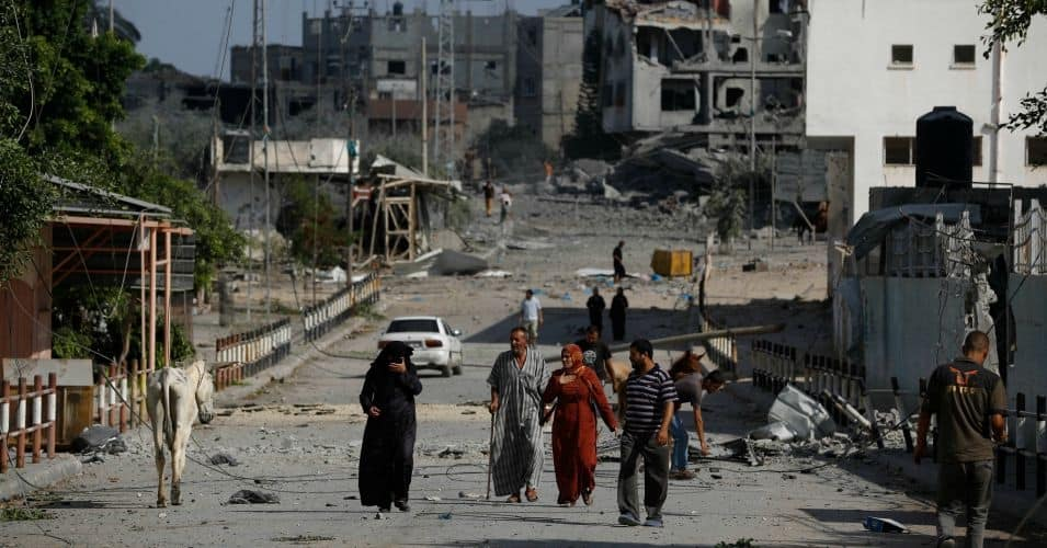 Families walk through the heavily-bombed area of Shujaiya in eastern Gaza on July 27, 2014.  (Photo: Iyad al Baba/Oxfam/flickr/cc)