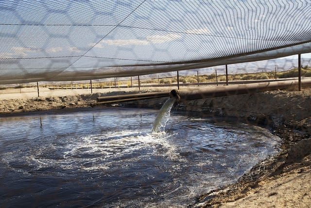Fracking fluid and other drilling wastes are dumped into an unlined pit located right up against the Petroleum Highway in Kern County, California.   Photo Credit: Sarah Craig/Faces of Fracking