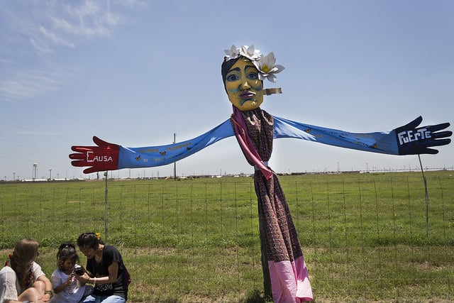 Rally to #EndFamilyDetention in Dilley, Texas Giant puppet in front of Dilley family detention center, run by CCA, Corrections Corporation of America for Immigration & Customs Enforcement (ICE). (Photo: UMWomen @ Flickr/cc)