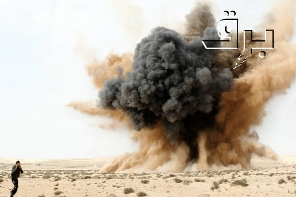 A rebel holds his ears as a bomb launched by a Libyan air force jet loyal to Libya's leader Muammar Gaddafi explodes in the desert near Brega, March 2, 2011.  (Photo BRQ Network @ flickr/cc)